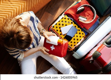 Upper view of modern woman in white pants and striped blouse at modern home in sunny summer day packing first aid kit and SPF in open travel suitcase.