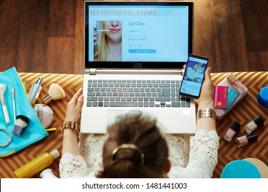 Upper view of modern woman in white dress using beauty cosmetics online store on a laptop and holding smartphone with ecommerce social media post while sitting on couch in the modern living room.