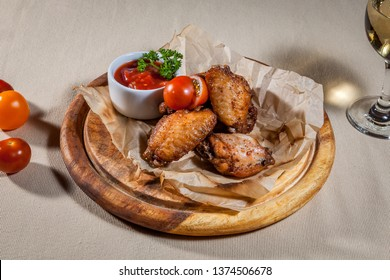 Upper view on circle wooden cutting board with pieces of baked chicken legs on paper, few cherry tomatoes, ketchup in sauce boat with branch of dill and wineglass of white wine
