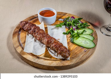 Upper view on circle wooden cutting board with pork kebab on pita, slices of fresh cucumber, finely chopped red onion, sprig of parsley, sauce board with ketchup and wineglass of red wine