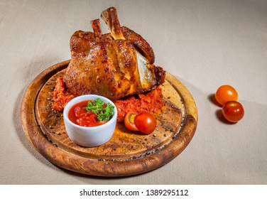 Upper view on circle wooden cutting board with baked chicken carcass on mashed tomato, sauce boat with ketchup and dill, and few cherry tomatoes
