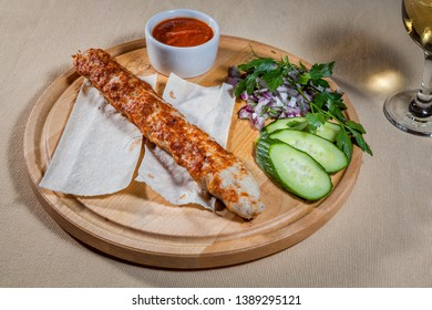 Upper view on circle wooden cutting board with chicken kebab on pita, slices of fresh cucumber, finely chopped red onion, sprig of parsley, sauce board with ketchup and wineglass of white wine