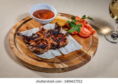 Upper view on circle wooden cutting board with quail carcass on pita, few slices of tomato, sprig of parsley, ketchup in sauce boat and wineglass of white wine