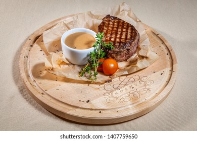 Upper view on circle wooden cutting board with piece of grilled beef on paper, decorated with sprigs of basil, cut cherry tomato, kitchen herbs and sauce boat with mustard sauce