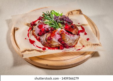 Upper view on circle wooden cutting board with slices of baked ham on paper with lettuce leaf, decorated with sprig of rosemary and cranberry sauce
