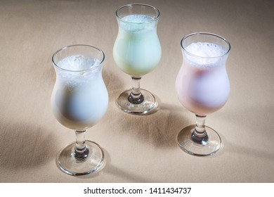 Upper view on three glasses of colored milk shakes: red strawberry, green kiwi and white vanilla, all standing on beige tablecloth