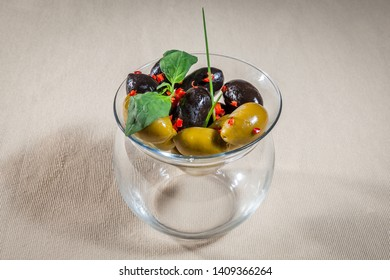 Upper view on transparent vase with black and green olives decorated with tine pieces of paprika, green onion leaves and sprig of mint