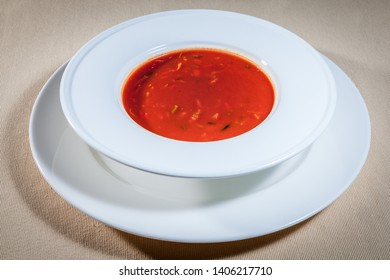 Upper view on white bowl on big saucer with Italian tomato soup on beige tablecloth