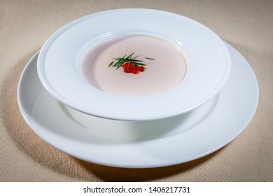 Upper view on white bowl with fish cream soup decorated with green flavoring and red caviar standing on big white saucer