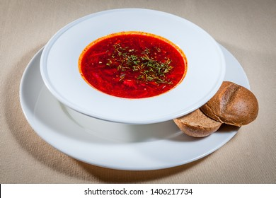 Upper view on white bowl on big saucer with Ukranian borsch with addition of finely chopped dill and cut rye bun