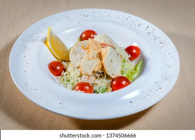 Upper view on white circle plate with vegetable salad consists of: cabbage, grated cheese, slices of toast and other veggies decorated by cut cherry tomatoes, slice of lemon and kitchen herbs