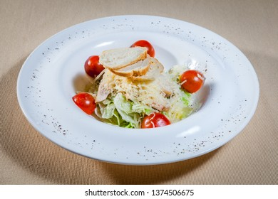Upper view on white circle plate with vegetable salad consists of: cabbage, grated cheese, slices of toast, pieces of boiled chicken and other veggies decorated by cut cherry tomatoes and kitchen herb