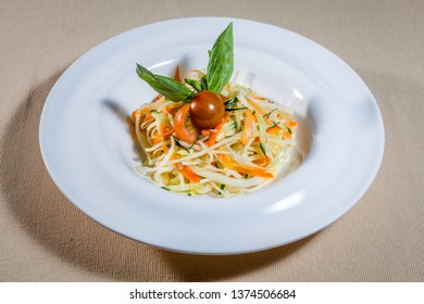 Upper view on white circle plate with vegetable salad consists of: cabbage, fresh cucumber and carrot decorated by cut cherry tomato and leaves of mint