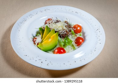 Upper view on white circle plate with vegetable salad consists of: cabbage, grated cheese, slices of avocado and some meat decorated by cut cherry tomatoes and kitchen herbs