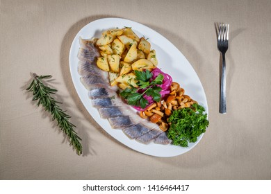 Upper view on white oval plate with slices of salted herring, fried potato, marinated honey agaric mushrooms and red onion rings, with sprigs of parsley, dill and rosemary, and fork
