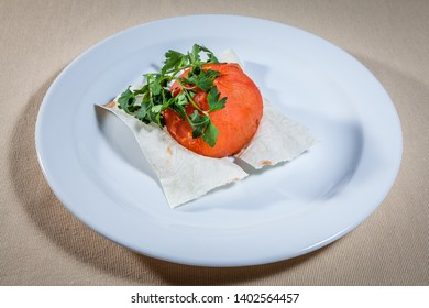 Upper view on white plate with whole skinless baked tomato on pita decorated with sprigs of parsley