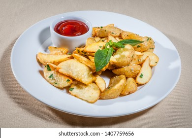 Upper view on white plate with slices of fried potato (Idaho potato), sauce boat with ketchup and sprig of mint