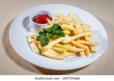 Upper view on white plate with sticks of fried potato (French fries), sauce boat with ketchup and sprig of parsley