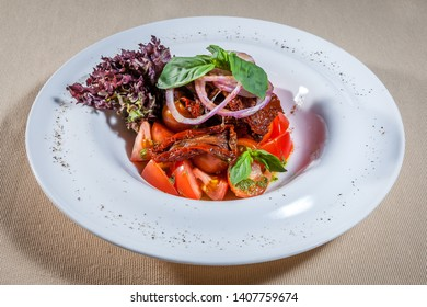 Upper view on white plate with vegetable salad cosists of: tomato, stewed paprika, marinated red onion and lettuce leaf, decorated with sprig of mint and kitchen herbs
