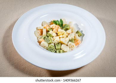 Upper view on white plate with colored boiled pasta decorated with sprig of parsley