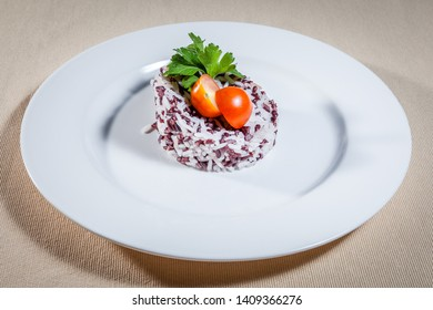 Upper view on white plate with steamed rice of two sorts: white and wild purple, decorated with sprig of parsley and cut cherry tomato
