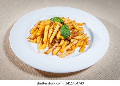 Upper view on white plate with sticks of fried potato (French fries) and sprig of mint as decoration