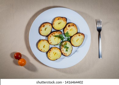 Upper view on white plate with half of tubers of baked potato with addition of cherry tomatoes and fork