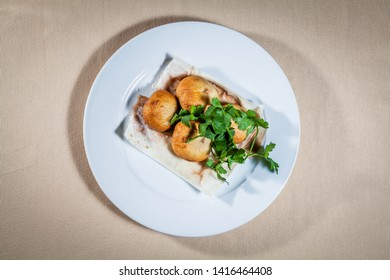 Upper view on white plate with whole tubers of baked potato on pita decorated with sprigs of parsley