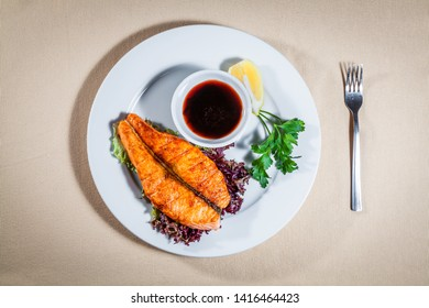 Upper view on white plate with grilled salmon on leaves of salad, soy sauce in sauce boat, slice of lemon, sprig of parsley and fork