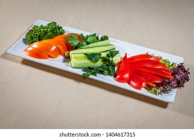Upper view on white rectangular plate with slices of fresh vegetables: tomato, cucumber and paprika with addition of salad leaves and sprigs of parsley and dill
