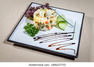 Upper view on white rectangular plate with Russian salad consists of: marinated cucumber, boiled carrot, peas, boiled potato and meat decorated with dill sprig, slice of fresh cucumber, salad leaf