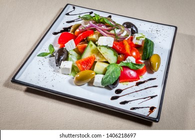 Upper view on white rectangular plate with vegetable salad consists of: cherry tomato, cucumber, paprika, feta cheese, red onion rings, green and black olives, decorated with mint sprigs