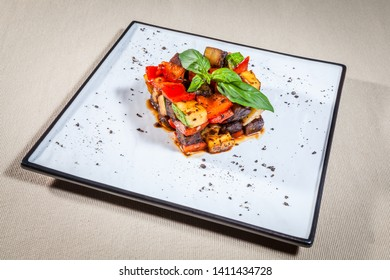 Upper view on white rectangular plate with traditional French cuisine dish ratatouille consists of stewed vegetebles: potato, vegetable marrow, aubergine, tomato and paprika, decorated with mint sprig