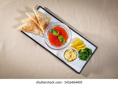 Upper view on white rectangular plate with different snacks: wheat toasts, red caviar with mint in trasparent vase, dill, slices of lemon and butter in oiler