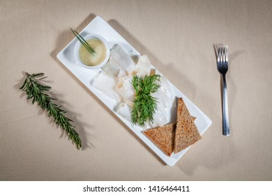 Upper view on white rectangular plate with slices of lard, oil sauce, dill, rosemary, toasts of rye bread and fork