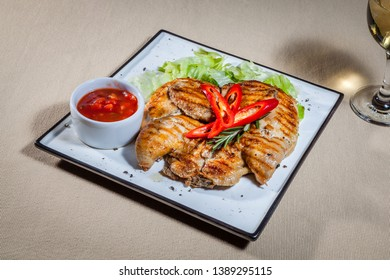 Upper view on white square plate with pieces of grilled quail carcass, slices of paprika, finely chopped cabbage, ketchup in sauce boat and wineglass of white wine