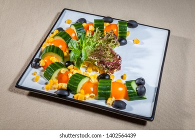 Upper view on white square plate with vegetable salad consists of: cabbage, cut cherry tomato, cucumber, olives, corn and leaves of mint, on tablecloth