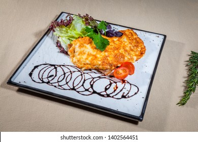 Upper view on white square plate with stewed pork under melted cheese, all decorated with leaves of cabbage and parsley, cut cherry tomato, soy sauce, kitchen herbs and sprig of rosemary