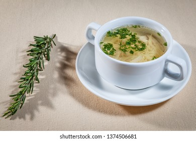 Upper view on white tureen on plate with transparent bouillon with noodles and branch of rosemary