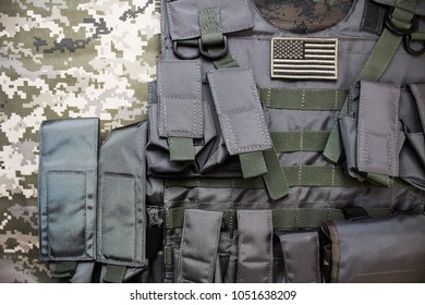 Upper view photo of tactical military bulletproof vest with american flag badge laying on camouflage cloth background.