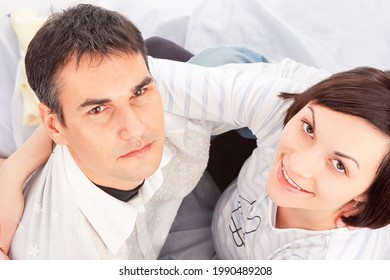 Upper View of Portrait of Caucasian Family Couple With Pregnant Woman Sitting Embraced Against White Background. Horizontal Shot - Shutterstock ID 1990489208
