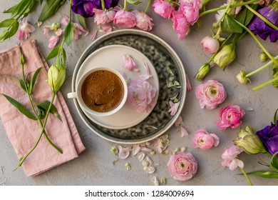 Upper view shot of a cup of coffee in the middle of floral frame of pink ranunculus and purple and yellow lisianthus