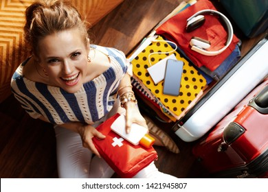 Upper view of smiling young woman in white pants and striped blouse with first aid kit near open travel suitcase at modern home in sunny summer day.