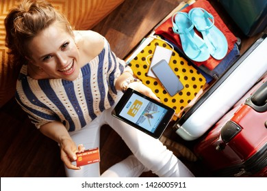 Upper view of smiling young woman in white pants and striped blouse at modern home in sunny summer day buying tickets online on tablet PC near open travel suitcase.