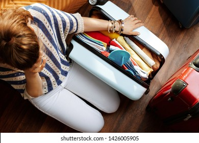 Upper view of stressed elegant woman in white pants and striped blouse in the modern living room in sunny summer day near over packed suitcase.