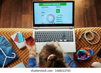 Upper view of trendy housewife in blue blouse sitting on sofa in the modern living room holding creme and writing review on laptop after beauty online shopping.