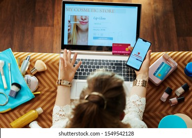 Upper view of trendy housewife in white dress with credit card buying makeup while shop online on a laptop and suffering from online shopping fraud while sitting on couch in the modern living room.
