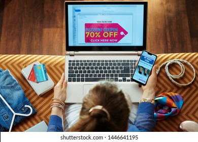 Upper view of young housewife in blue blouse browsing shoe retail online store on a smartphone and got email with discount coupon on a laptop while sitting on couch in the modern living room.