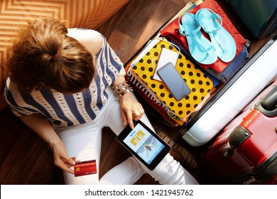 Upper view of young woman in white pants and striped blouse at modern home in sunny summer day book flight on tablet PC near open travel suitcase.