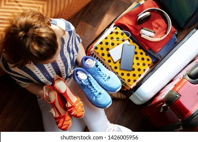 Upper view of young woman in white pants and striped blouse at modern home in sunny summer day packing fashion and comfortable shoes in open travel suitcase.